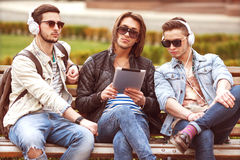 Three young men friends using tablet Stock Images