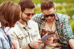 Three young men friends using tablet Royalty Free Stock Image