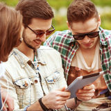 Three young men friends using tablet Royalty Free Stock Photos