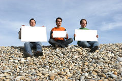 Three Young Men Holding White Cards. At the beach stock image