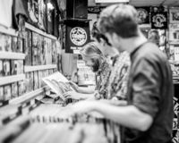 Young men looking at vinyl records in a store or shop. stock photos