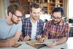 Three Young Men in Modern Office Stock Photo
