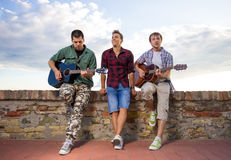 Three young men music band playing outdoors sunny Stock Image