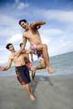 Three young men playing with a ball on a beach Stock Photography