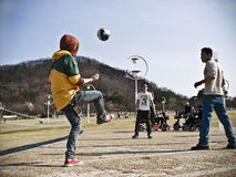Three young men playing football in a korean park Stock Photo