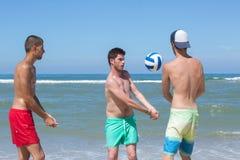Three young men playing handball on beach Royalty Free Stock Photo