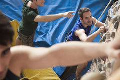 Three young men point and climbing in an indoor climbing gym Stock Images