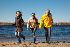 Three young men running down beach at camera Stock Photography