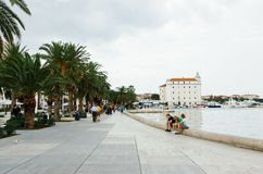 Three young men sit on the Adriatic sea promenade, relax and talk. September 22, 2011, Trogir city, Croatia. Three young men sit on the Adriatic sea promenade Royalty Free Stock Images