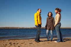 Three young men stand on bank of river Stock Images