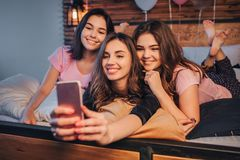 Three young models taking selfie. They pose and smile. Gils are in room. One of them hold phone and take picture on it stock images