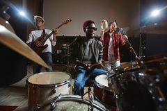 Young band. Three young musicians playing musical instruments and performing songs in studio of records stock image
