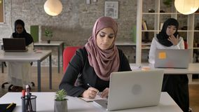 Three young muslim womans in hijab sitting and typing on laptop in modern office, black woman in hijab working.  stock footage