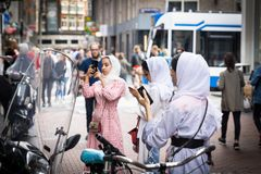 Three young Muslim women in white hijab in busy city street Royalty Free Stock Image