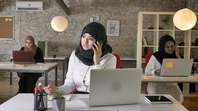 Three young muslim womens in hijab sitting and typing on laptop in modern office, beautiful muslim woman talking on stock video footage