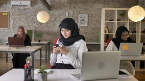 Three young muslim womens in hijab sitting and typing on laptop in modern office, charming female worker texting on. Phone stock video footage