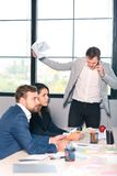 Three office workers for an interview, an angry man talking on the phone, and holding documents in his hand. stock images