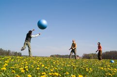 Three young people with ball. Three young people playing with big ball on the spring meadow Stock Photos
