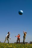 Three young people with ball. Three young people playing with big ball on the spring meadow Stock Photography