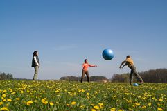 Three young people with ball. Three young people playing with big ball on the spring meadow Stock Photo