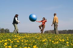 Three young people with ball. Three young people playing with big ball on the spring meadow Royalty Free Stock Photos