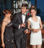 Three young people at bar drinking and flirting. Three young people at a bar, men in black tuxedo holding whisky in his hand, women with hairstyle in black and Royalty Free Stock Photos