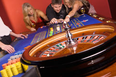 Three young people in casino. Three young people playing roulette in casino Stock Images