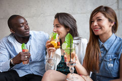 Three young people with cocktail. At bar Royalty Free Stock Photos