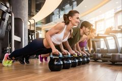 Three young people doing the kettlebell plank challenge during g Stock Photos