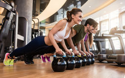 Three young people doing the kettlebell plank challenge during g Royalty Free Stock Image