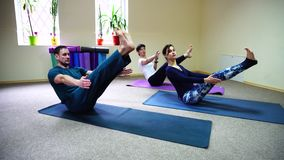 Three young people doing yoga at fitness studio. Two women and men of American appearance engaged in yoga, people sit on floor on fitness rugs and perform stock video