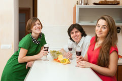 Three young people drink wine Stock Images