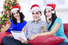 Three young people drinking champagne at home. Smiling three young people wearing santa hat drinking champagne at home Royalty Free Stock Images