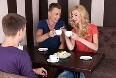 Three young people drinking coffee. Royalty Free Stock Photo