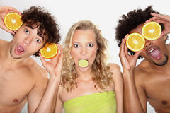 Three young people have fun with fruits Royalty Free Stock Photos