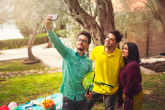 Three young people make selfi under the olive tree Royalty Free Stock Photos