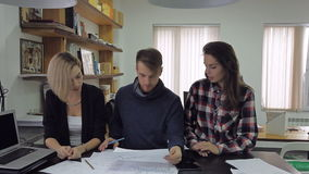 Three young people in the office discussing results presented in graphs and charts. These are two beautiful women and a man in a fashionable blue sweater. They stock footage