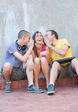 Three young people outdoors. Three young people having fun outdoors. Boys whispering something in girl's ears, making her smile Royalty Free Stock Photo