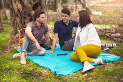 Three young people on picnic sitting on blanket under the olive Royalty Free Stock Images