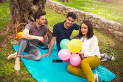 Three young people on picnic sitting on blanket under the olive trees Stock Photo