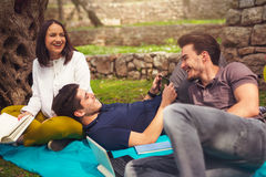 Three young people on picnic under the olive trees Stock Image
