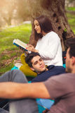 Three young people on picnic  under the olive trees Royalty Free Stock Photo