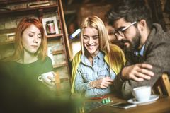 Game. Three friends at cafe. Three young people playing leisure game. Three friends at cafe Stock Image