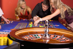 Three young people playing roulette. In casino Royalty Free Stock Photos