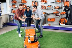 Three young people are posing with a lawn mower. Stock Photography