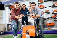 Three young people are posing with a lawn mower. Stock Images