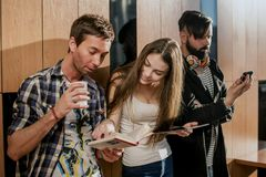Three young people in the room. People standing near the wall with gadgets in their hands. Stock Photo