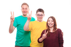 Three young people showing victory sign and smiling Stock Photos