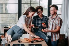 Three young people sitting around and eating pizza. Friends part. Ying at home. Friendship, togetherness, lifestyle, people and eating concept Stock Photo