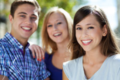 Three young people smiling. Portrait of young people outdoors Stock Image